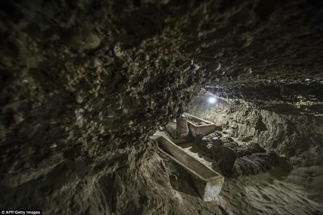 Mummies are pictured next to open coffins in one of the tomb's passageways