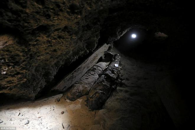 Light shines into one of the burial site's many tunnels, where two mummies can be seen.