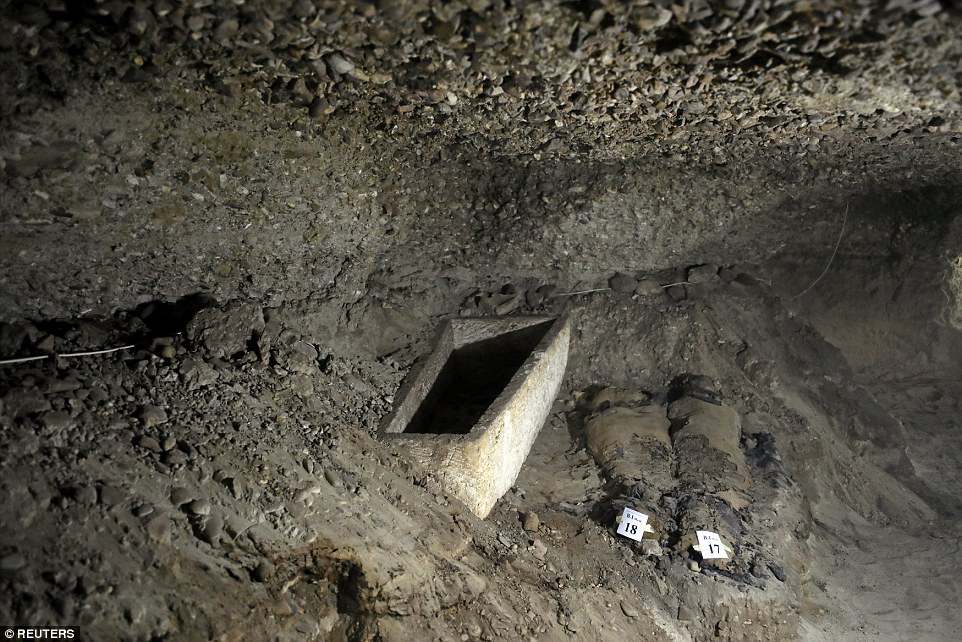 Two of the mummies are pictured next to a tomb inside the burial site.