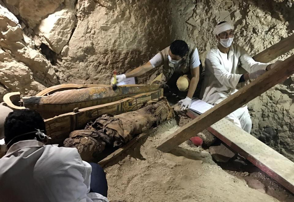 archaeologists wearing white masks and latex gloves inspected the coffins