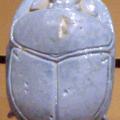 Un medaillon de pierre taillee en forme de scarabee